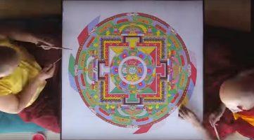 monjes tibetanos realizando mandala con arena coloreada