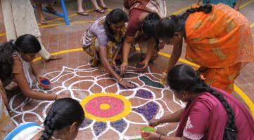 niñas indias coloreando un mandala pintado en el suelo